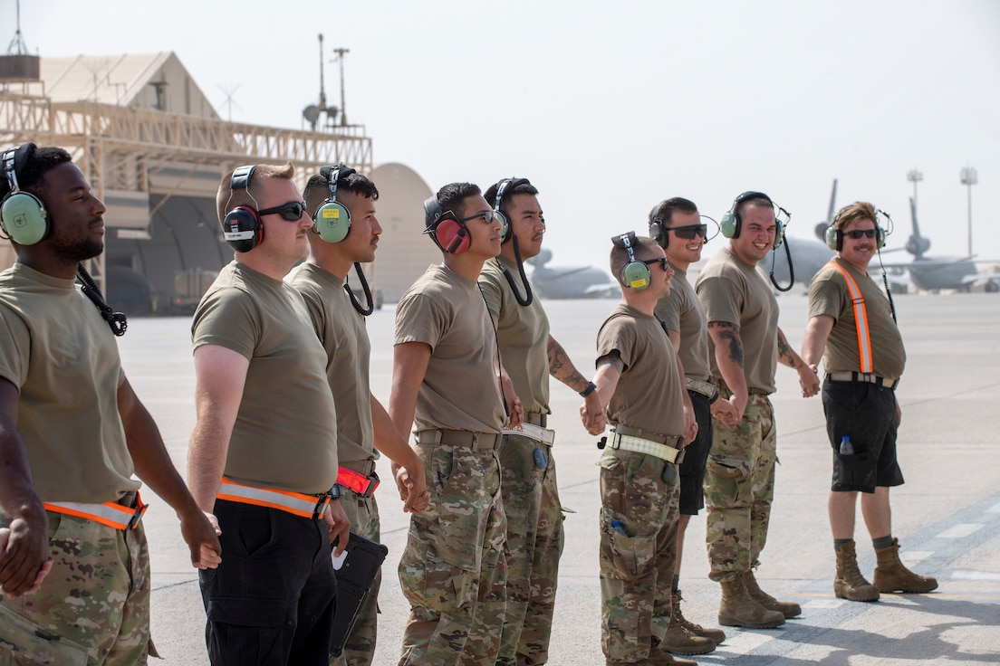 Airmen holding hands in a line on the flight line
