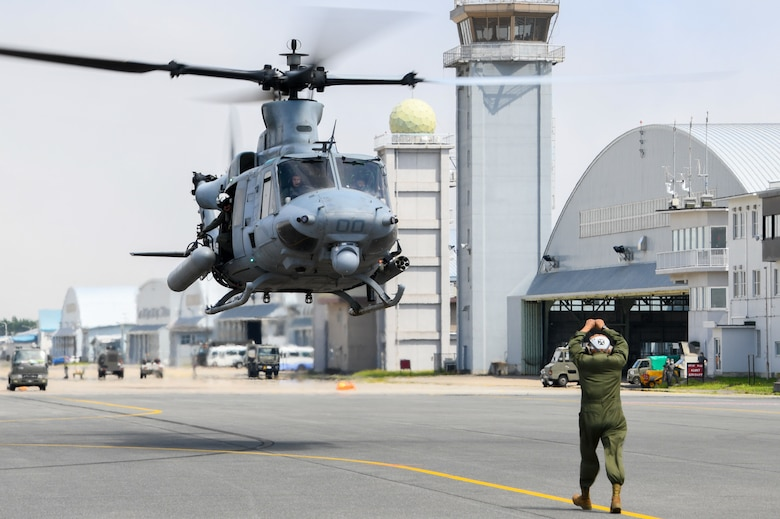 A man in uniform uses hand signals to communicate with a helicopter in flight.