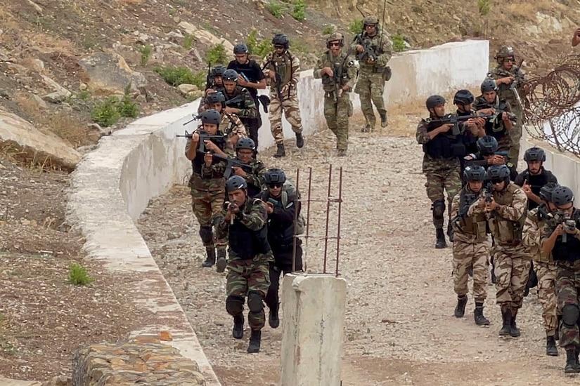 Troops move along a dirt road.