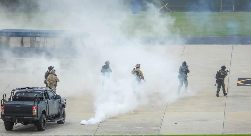 Troops move through smoke.