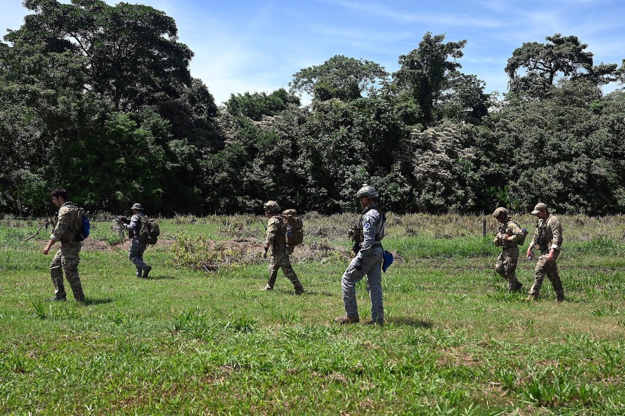 Soldiers walk across a field.