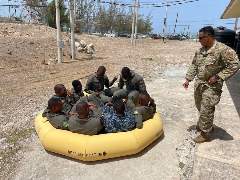 U.S. Air Force Tech. Sgt. Gerame Vaden, 571st Mobility Support Advisory Squadron air advisor, instructs Jamaican Defense Force Air Wing aircrewmen on life raft inflation and embarkation on land prior to moving to the water June 16, 2021, at the Caribbean Military Aviation School, Kingston, Jamaica.  Air advisors train and assist partner nations in developing air mobility capabilities through Mobile Training Team engagements. (Courtesy photo)