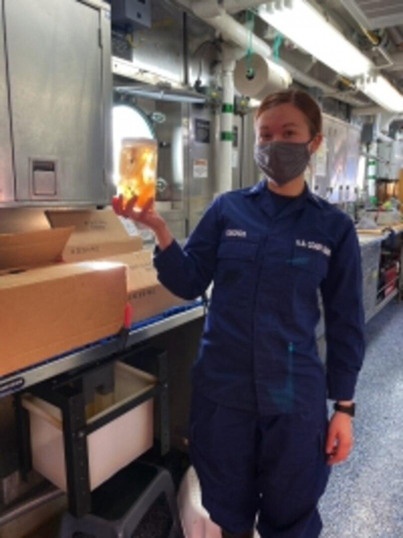Serving aboard NOAA Ship Reuben Lasker, U.S. Coast Guard officer Lt.j.g. Rebecca Edmonds holds a sample of plankton that is submerged in a preservation fluid