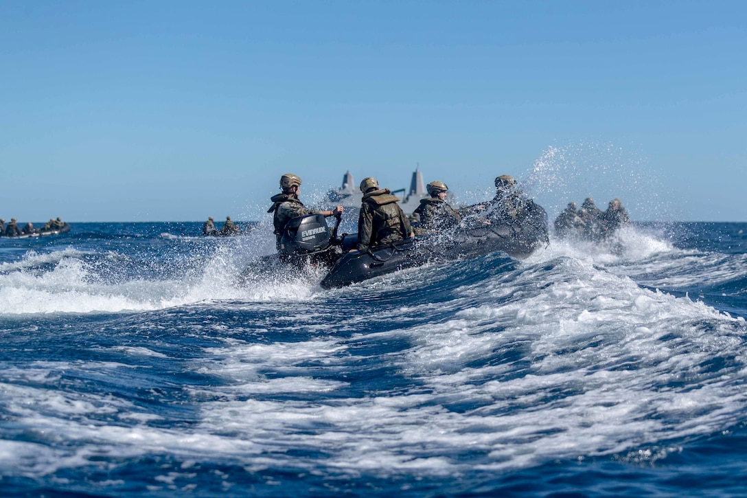 Marines float in the ocean on rubber crafts.