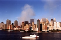 The World Trade Center complex continues to burn, while the Coast Guard Cutter Tahoma controls vessel traffic in New York harbor September 15.