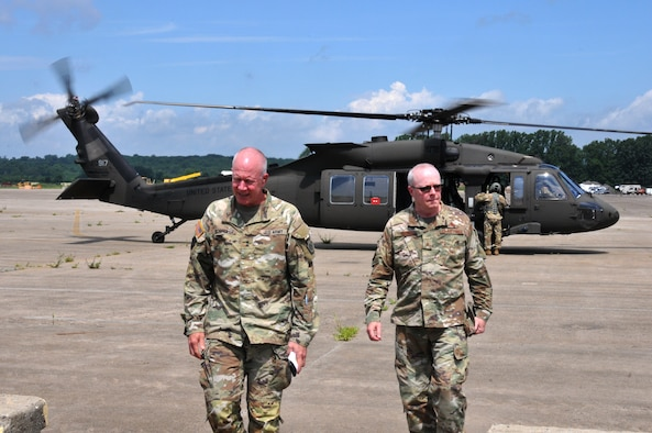 Two men in OCP Air Force uniform deboarding an helicopter.