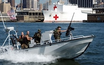 """""""A Coast Guard Port Security boat races to question a recreational vessel on the Hudson River in New York. Coast Guard vessels are deployed around Manhattan to ensure the safety of New York city's waterways.""""; 19 September 2001; CG# 010910-C-9409S-501 (FR); photo by PA2 Tom Sperduto."""
