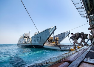 Marines assigned to the 24th Marine Expeditionary Unit (MEU) board Landing Craft, Utility (LCU) 1661, attached to Assault Craft Unit (ACU) 2, from the well deck of the dock landing ship USS Carter Hall (LSD 50)