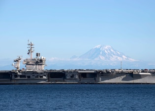 The Nimitz-class aircraft carrier USS Theodore Roosevelt (CVN 71) transits through the Puget Sound to its new homeport of Bremerton, Washington.