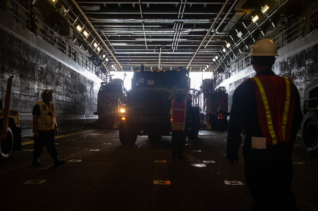 U.S. Marines and Sailors load a medium tactical vehicle replacement onto a landing craft, air cushion aboard the USS Arlington (LPD-24) during Defense Support of Civil Authorities (DSCA) mission rehearsals at Naval Base Norfolk, Virginia, July 22, 2021. Marines and Sailors with the II Marine Expeditionary Force Maritime DSCA Task Force, commanded by Combat Logistics Battalion 22, and Sailors aboard the USS Arlington conducted a destructive weather mission rehearsal loading exercise to prepare and rehearse for a future DSCA mission during the 2021 hurricane season. (U.S. Marine Corps photo by Lance Cpl. Scott Jenkins)