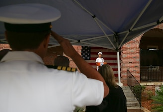 """Lt. Cmdr. Kimi Schultheiss sings the national anthem during the Naval Education and Training Command (NETC) 50th anniversary ceremony at Naval Air Station Pensacola.  NETC, led by Rear Adm. Pete Garvin, is the U.S. Navy's Force Development pillar and largest shore command.  Through its """"Street to Fleet"""" focus, NETC recruits civilians and transforms them into skilled warfighters ready to meet the current and future needs of the U.S. Navy."""