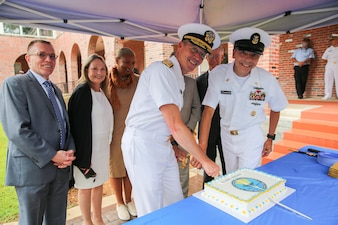 """Rear Adm. Pete Garvin, commander, Naval Education and Training Command (NETC), center, and Force Master Chief Matthew Harris, right, cut a cake with former commanders and force master chiefs to celebrate NETC's 50th anniversary following a ceremony at Naval Air Station Pensacola.  NETC is the U.S. Navy's Force Development pillar and largest shore command.  Through its """"Street to Fleet"""" focus, NETC recruits civilians and transforms them into skilled warfighters ready to meet the current and future needs of the U.S. Navy."""