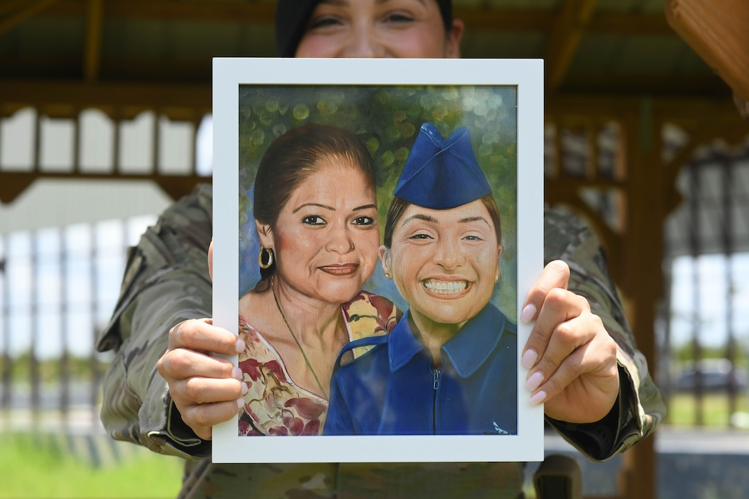 Airman 1st Class Jocelyn Soto holds a painting of her and her mother.