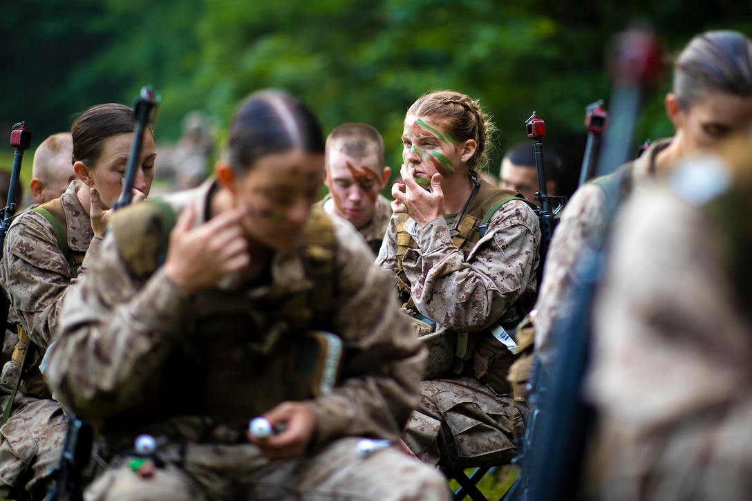 A group of Marines apply face paint.
