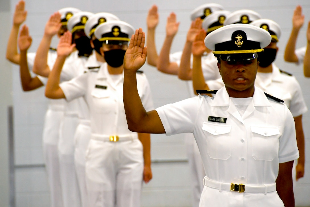 Navy ROTC midshipmen raise their right hands while standing in formation.