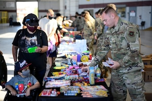Airmen, parents and students line up along a string of tables to look over a selection of free school supplies during the Back-to-School Brigade July 23, 2021, at Travis Air Force Base, California. The school supplies are given away for free as part of the base's annual tradition of ensuring all returning students have the resources they need ahead of the start of the new school year. (U.S. Air Force photo by Staff Sgt. Christian Conrad)