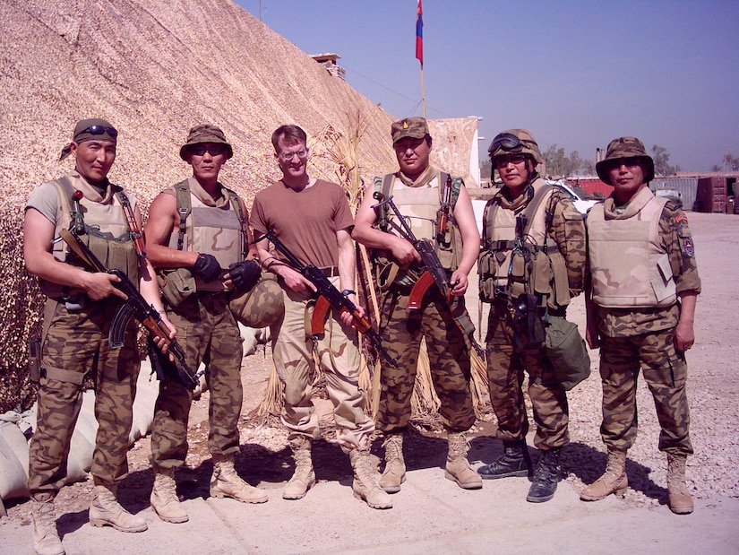 Lt. Col. Steve Wilson poses for a photo with his Mongolian counterparts in Iraq in 2004. Wilson was the first liaison to accompany the Mongolian Armed Forces on a deployment during the Global War on Terrorism as part of the state partnership program. The SPP is a program that links a state's National Guard with the armed forces or equivalent of a partner country in a cooperative, mutually beneficial relationship. (Courtesy photo)