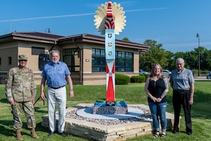 (From left to right) Col. Nate Vogel, 22nd Air Refueling Wing commander, Vincent Fredericksen, 22nd Civil Engineer Squadron base architect, Angie Evans, Wichita artist, and Jack Pulley, president of Friends of McConnell, pose for a photo next to the Keeper of the Plains replica donated to the base July 23, 2021, at McConnell Air Force Base, Kansas. The ten-foot-tall Keeper was donated by the Friends of McConnell organization and designed by Vincent Fredericksen, 22nd Civil Engineer Squadron base architect, and Staff Sgt. Trevor Bjelke, former 22nd Communications Squadron network infrastructure technician. (U.S. Air Force photo by Senior Airman Skyler Combs)