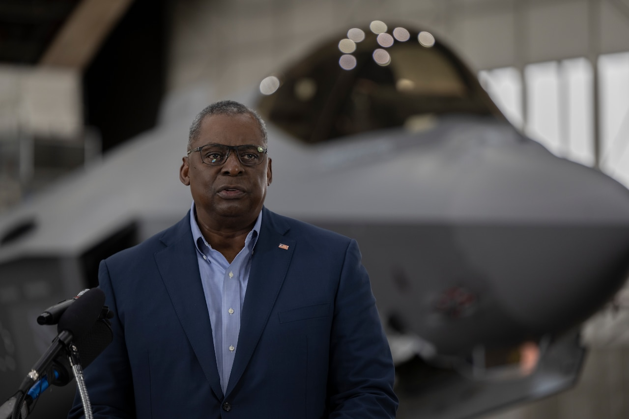 Secretary of Defense Lloyd Austin stands in front of a microphone.