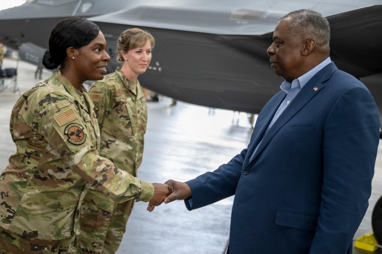 Secretary of Defense, Lloyd J. Austin III shakes hands with a service member.