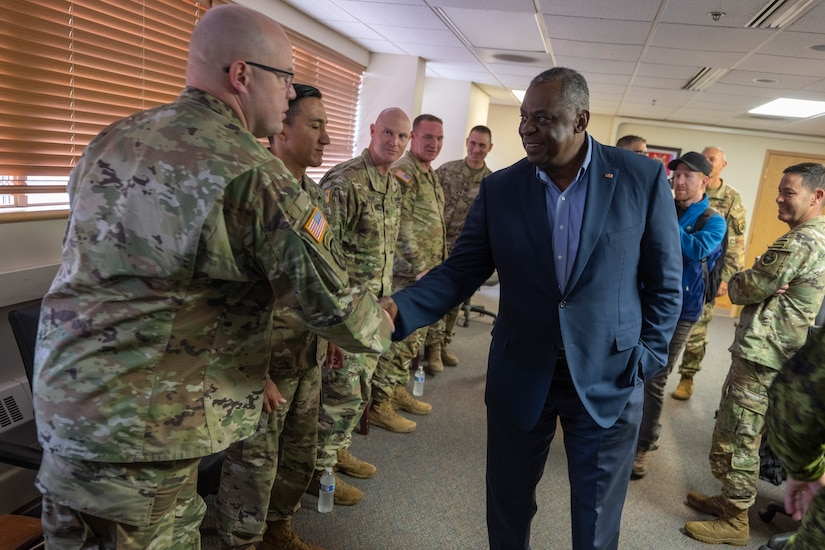 Secretary of Defense, Lloyd J. Austin III shakes hands with service members.
