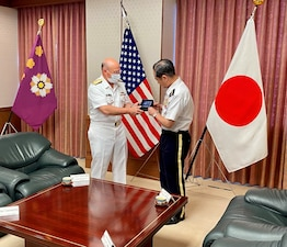 Chief of Naval Operations (CNO) Adm. Mike Gilday exchanges a gift with Japan Chief of Staff of the Joint Staff Gen. Koji Yamazaki at the Japan Ministry of Defense in Tokyo.