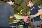 Tonneisha Scott, center, a sustainment specialist with Defense Logistics Aviation at Jacksonville, Florida's planning division, receives a visual of parts needed to repair the canopy on an F/A 18 Hornet with Scott Still, left, and Todd Hile, right, sheet metal mechanics with Fleet Readiness Center Southeast's Canopy Shop.