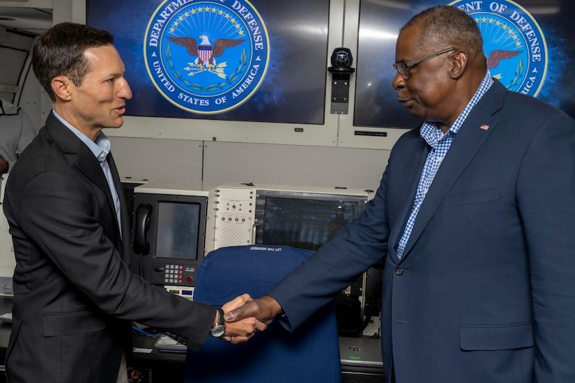 Two men shake hands.