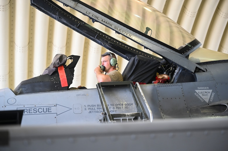 An Airman sitting in an airplane tests communications systems.