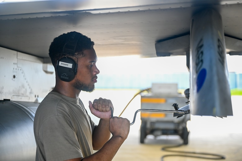 An Airman uses a tool on an F-16 Fighting Falcon airplane.