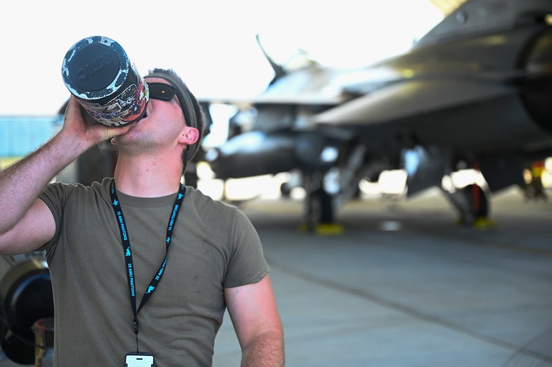 An Airman drinks from a water bottle.