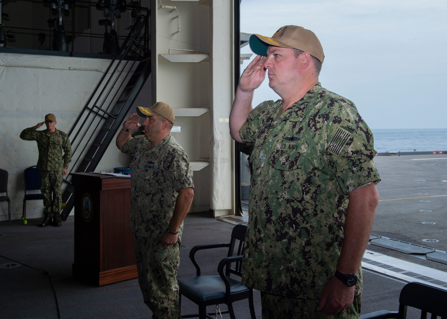 """Capt. Chad Graham, right, and Capt. David Gray, center, and Command Senior Chief Mark Rayner, left, participate in a change of command ceremony aboard the Expeditionary Sea Base USS Hershel """"Woody"""" Williams (ESB 4), July 25, 2021."""