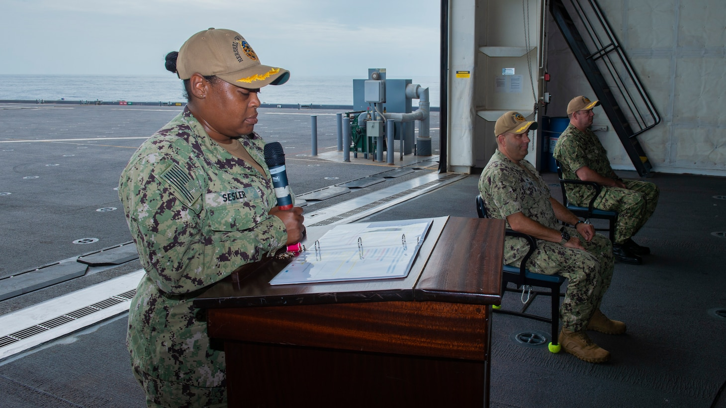 """Executive Officer Ernique Sesler, left, Capt. David Gray, center, and Capt. Chad Graham, right, participate in a change of command ceremony aboard the Expeditionary Sea Base USS Hershel """"Woody"""" Williams (ESB 4), July 25, 2021."""
