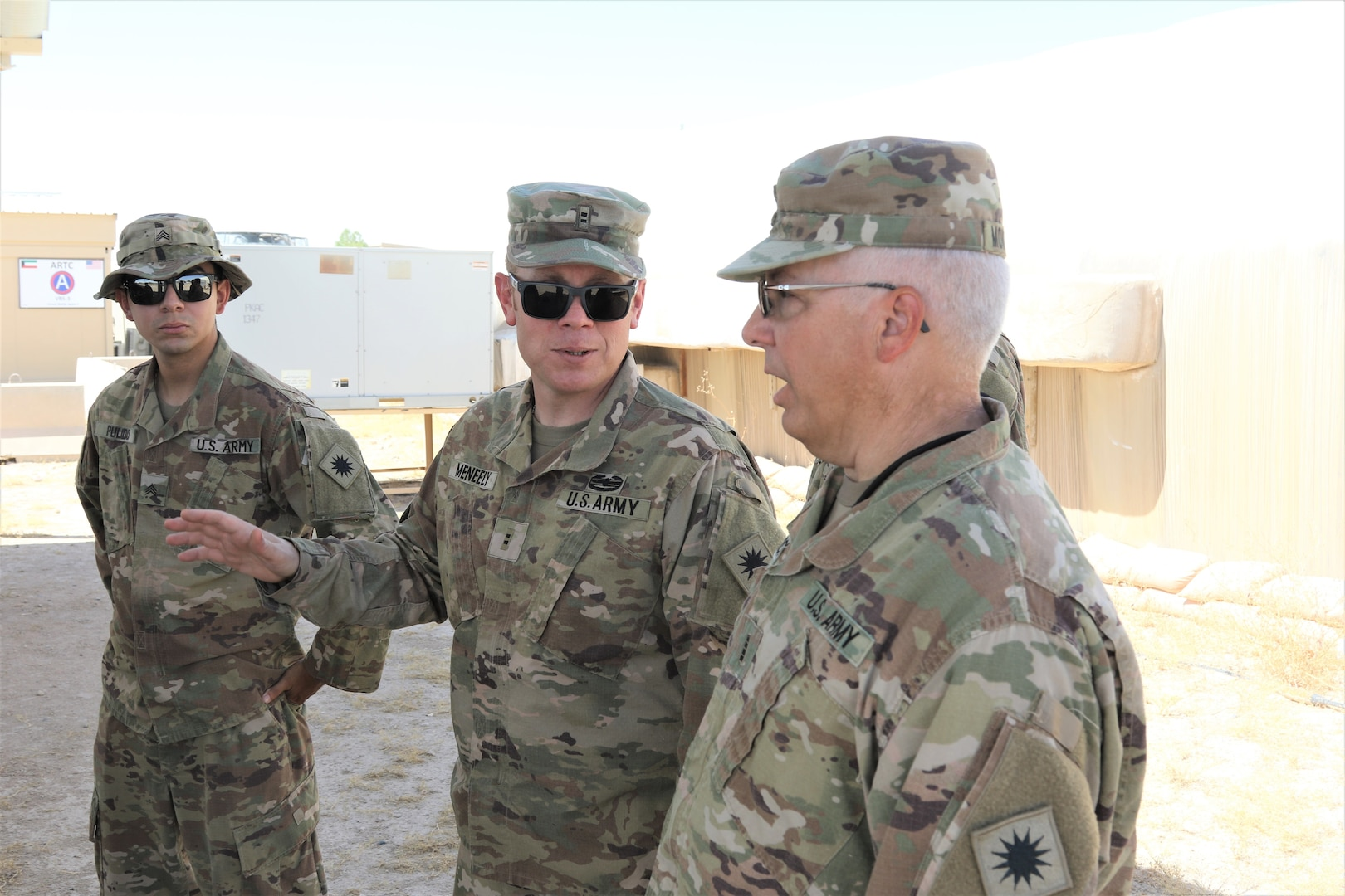 Sgt. Ismael Pulido, electronic warfare NCO, Chief Warrant Officer 2 Anthony Meneely, Chief Warrant Officer 4 Douglas Montgomery discuss Counter Radio-Controlled Improvised Explosive Device Warfare system training at Camp Buehring, Kuwait. Pulido, Meneely and Montgomery are the Task Force Phoenix Cyberspace Electromagnetic Activities cell.