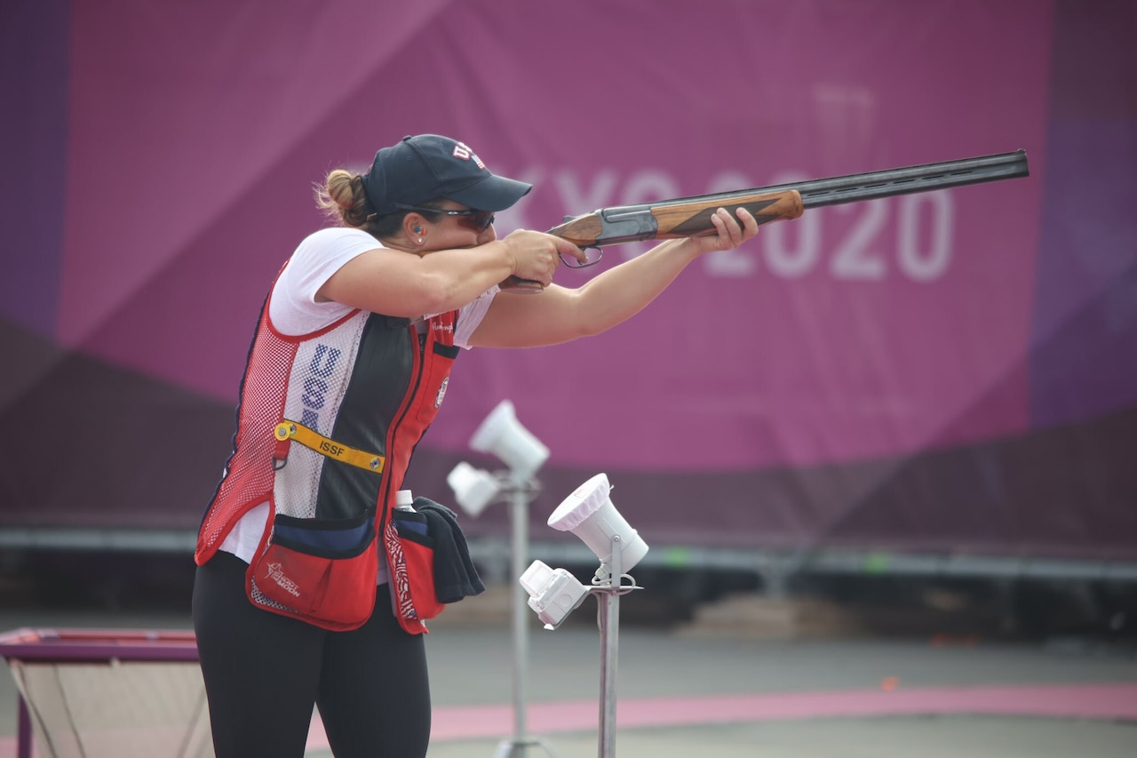 An athlete fires her weapon during a competition.