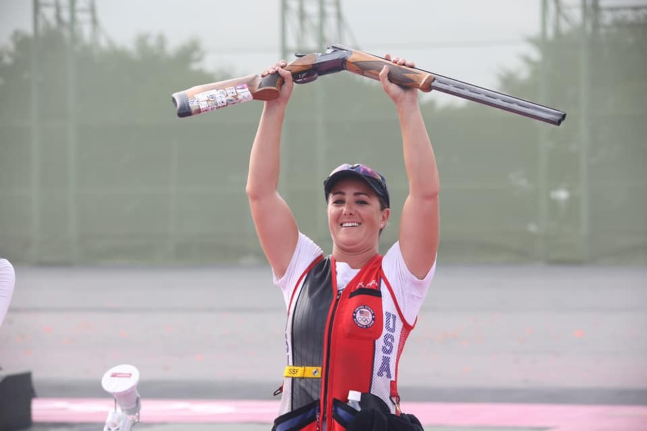 An athlete smiles as she holds a rifle above her head.