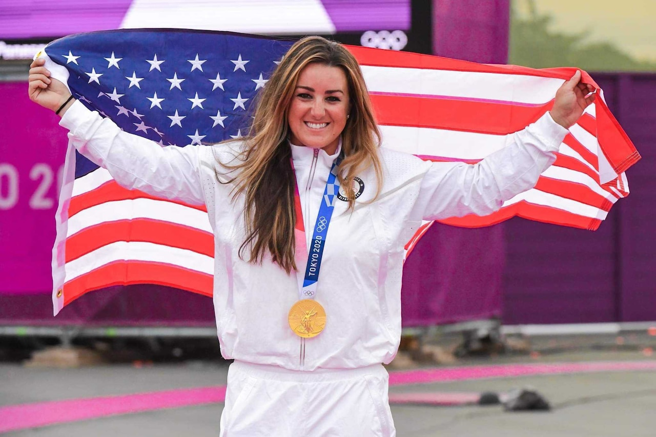 A female athlete smiles as holds the American flag.