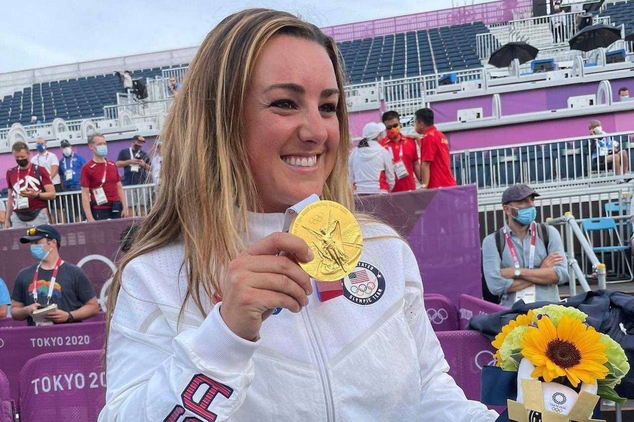 A female athlete smiles as hold a gold medal in her hand.
