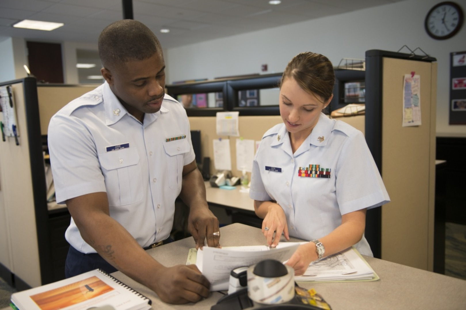 ARLINGTON, Va. - A Coast Guard yeoman assists a fellow Coast Guardsman at the Coast Guard Recruiting Command, February 20, 2013. YNs are key problem-solvers, counselors, and sources of information to personnel on questions ranging from career moves, entitlements, and incentive programs to retirement options and veterans' benefits. U.S. Coast Guard photo by Petty Officer 1st Class Luke Pinneo