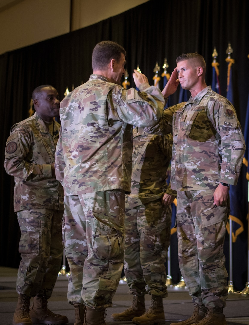 U.S. Air Force Senior Master Sgt. Mark Schneider II, right, of the 179th Airlift Wing, Ohio National Guard, salutes Lt. Gen. Michael A. Loh, director, Air National Guard, upon receiving a coin at the Air National Guard Senior Leader Conference in St. Louis, Missouri, July 20, 2021. Schneider, the ANG's outstanding senior noncommissioned officer of the year, was recognized for superior leadership, job performance and achievements.