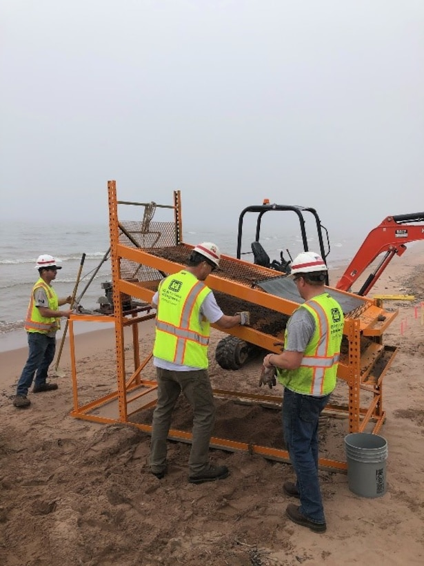 """U.S Army Corps of Engineers, Duluth Area Office Floating Plant crew designed and fabricated a screening machine to filter the debris from the beach on Minnesota Point.  The crew placed a larger 1"""" Screen on top and the bottom screen contained ¼"""" openings.  The crew placed the dredged material on the screen and utilized a vibrating mechanism and water to sort the rocks, wood debris and human made debris from the beach.  The crew has completed all required cleanup areas on the beach from the FY20 Dredging contract"""