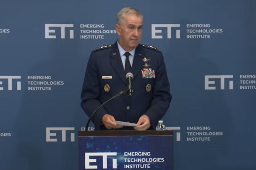 A man in a military uniform stands at a lectern holding a piece of paper.