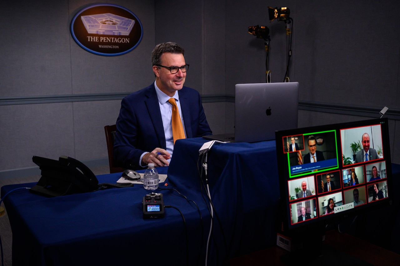 A man looks at a computer video camera during a video conference.The sign behind him indicates that he is speaking from the Pentagon.
