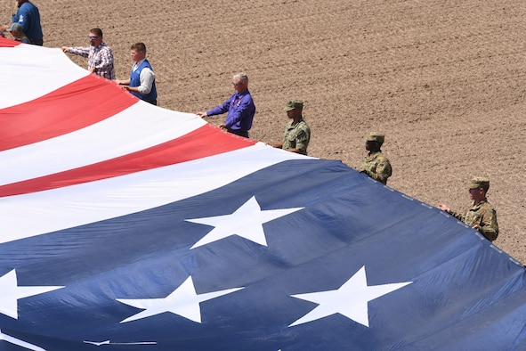 Members of the military and local community present the American flag during Military Monday at Frontier Park in Cheyenne, Wyo., July 26, 2021. The flag presentation is an annual tradition at Cheyenne Frontier Days and Military Monday honors those serving in the local community and provides an opportunity to showcase the strong relationship between the base and the local community.  (U.S. Air Force photo by Airman 1st Class Darius R. Frazier)