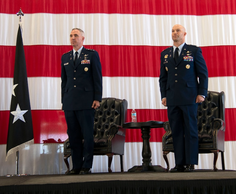 two men stand at attention on a stage