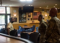 A civilian talks to two service members while standing in a restaurant area.