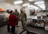 Civilians and service members talk to each other while standing next to a silver table in a kitchen area.