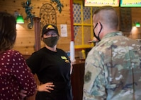 Civilians and a service member talk to each other.
