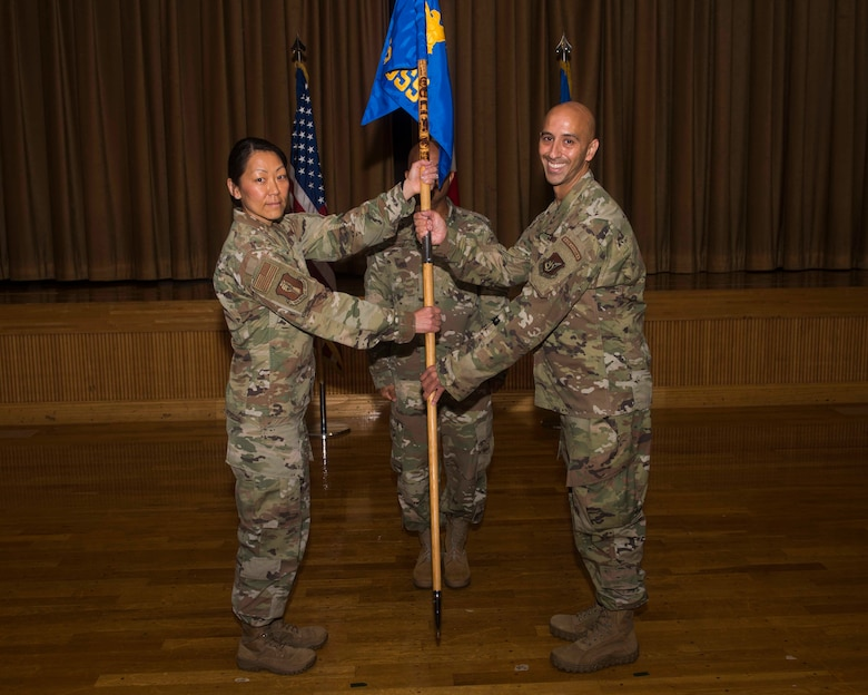 A female service member on the left passes a guidon to a male service member on the right.