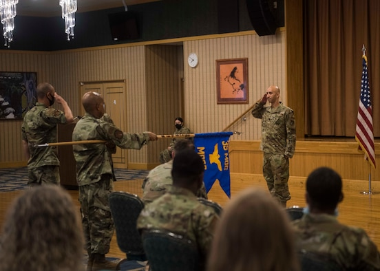 A service member on the right renders a salute to another service member and a guidon bearer while audience members watch.